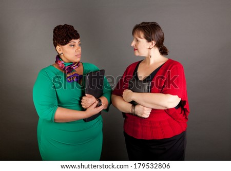 Two confident plus size business women staring at each other with tension in their faces - stock photo