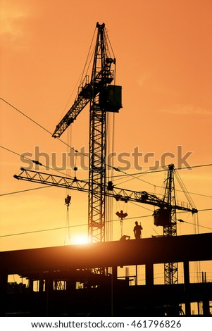 Two construction cranes and construction workers on site