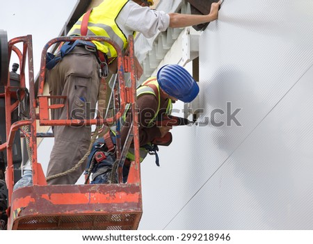 Two construction workers mounting facade panels on height