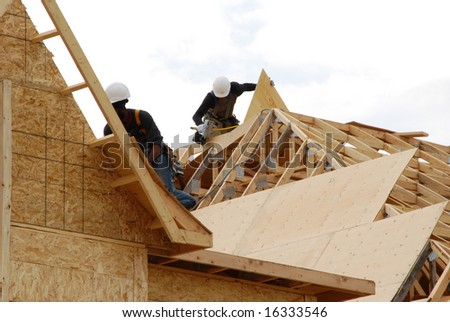 Two construction workers nailing  roof panels