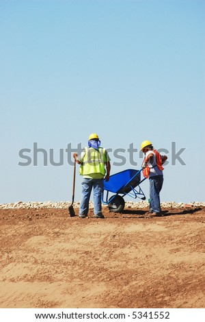 Two Construction Workers on hill with wheelbarrow, against blue sky