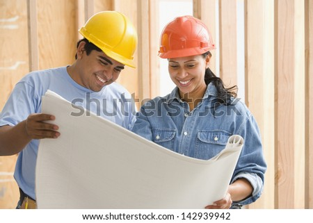 Two construction workers reading plans - stock photo