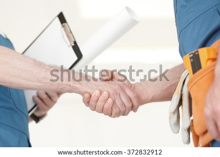Two construction workers shaking hands, deal is finished concept