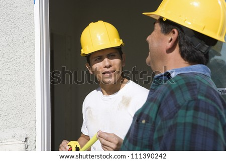 Two construction workers with measure tape - stock photo