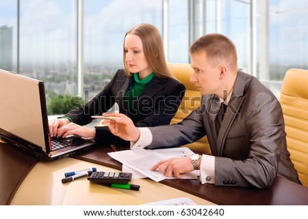 Two contemporary business people in office discussing work - stock photo