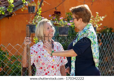 Two contented happy elderly ladies standing chatting together in the garden in the sunshine. - stock photo