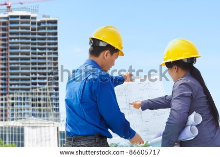 Two contractors, man and woman facing the building project in progress