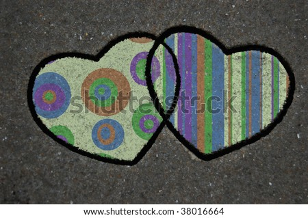 Two cookie cutter hearts in the sand with pattern overlay - stock photo