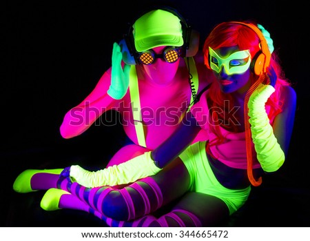 two cool disco glow characters pose in UV costume - stock photo