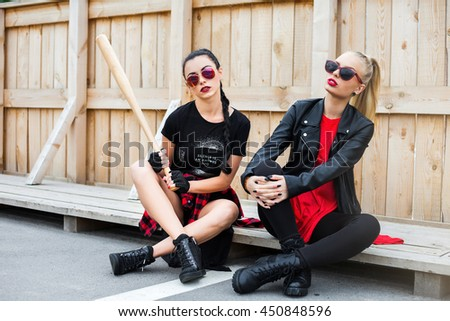 Two cool trendy bold hipster girl in casual black and red dress, sitting on a wooden background with baseball bat, blonde and brunette wearing sunglasses, shorts, T-shirts, leather jacket. Beauty Swag - stock photo