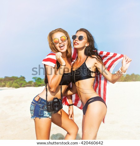 Two cool trendy hipster girls at the beach enjoying vacation on a tropical island, perfect tanned body, sexy stylish casual wear, bikinis, blonde and brunette with the camera, woman photographer - stock photo