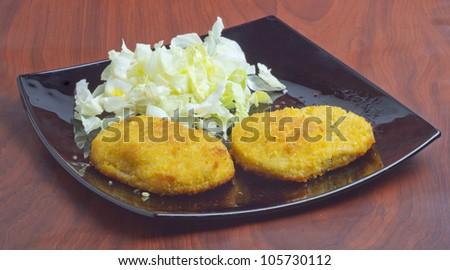 Two cordon bleus near some salad over a black plate - stock photo