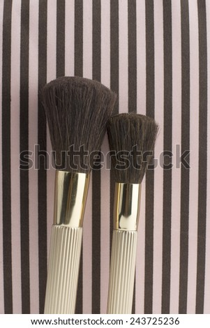 Two cosmetic brushes on the striped background - stock photo