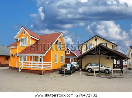 Two cottages and autos parked nearby - stock photo
