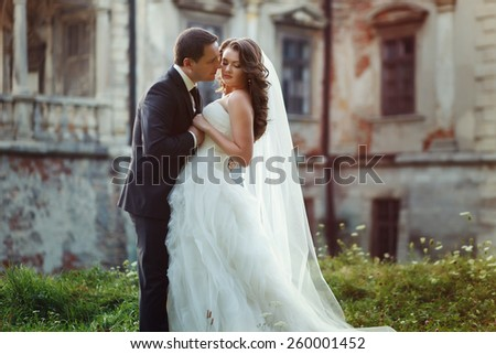 two couple after wedding in tne park near the castle - stock photo