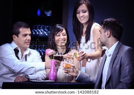 two couples by eating in a restaurant