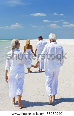 Two couples, generations of a family together holding hands and walking on a tropical beach - stock photo