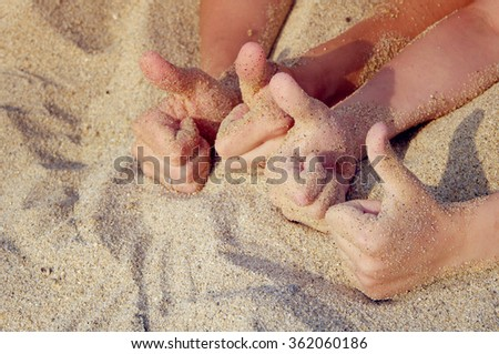 Two couples hands do the sign Like. The hands of mother and the child doing the sign Like on a beach in sand in a summer sunny day. Family rest.Thumbs up. Like - stock photo