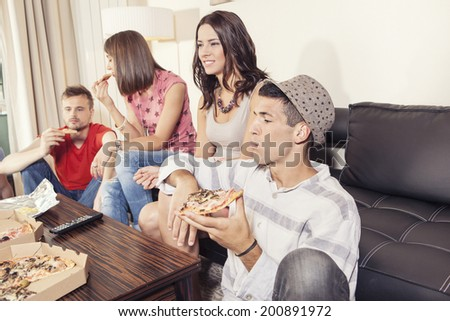 Two couples having fun,eating pizza, watching the game - stock photo