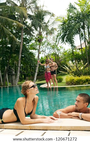 Two couples lounging and having fun by the edge of a swimming pool in a tropical destination hotel spa garden while on vacations. - stock photo