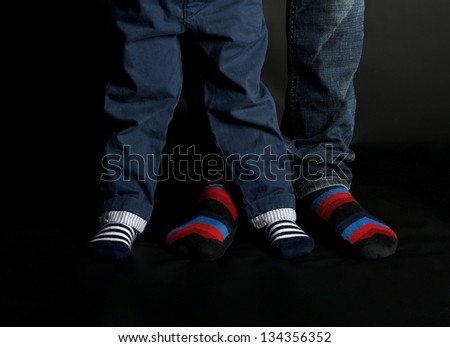 Two couples of legs in colorful socks, fathers and kids legs close up, body part, small and large legs in colorful socks close up, legs fragment in dar background, - stock photo