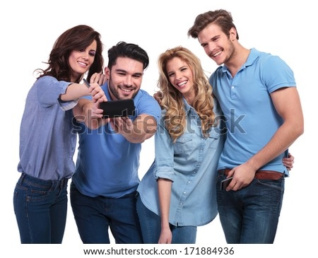 two couples of young people taking their picture with a phone on white background - stock photo