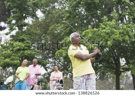 Two couples playing golf together - stock photo