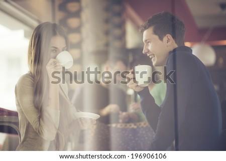 Two couples shot through window enjoying coffee  - stock photo