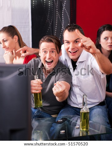 Two couples watching sports in the telly, the guys are really excited, drink beer and cheer their team while the girls are quite bored - stock photo
