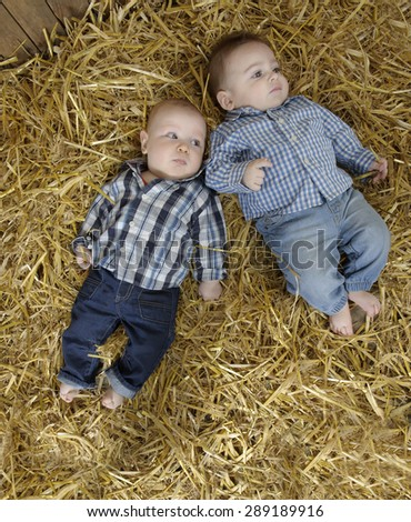 two cowboy baby boys lying in straw - stock photo
