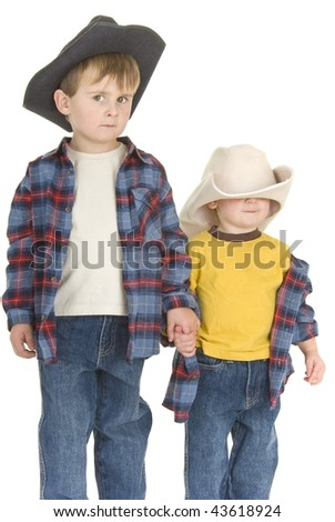 Two cowboy brothers hold hands looking curiously or suspiciously at camera