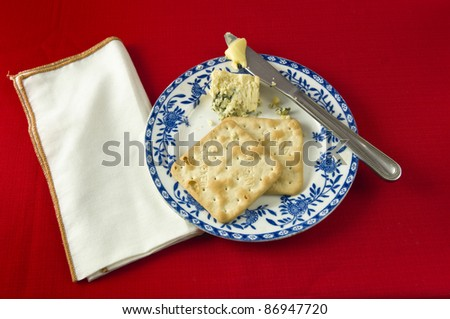 Two crackers and Stilton cheese on blue and white plate , with knife and butter. White napkin against red table cloth
