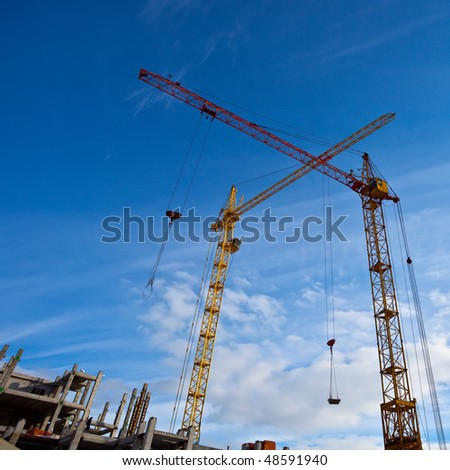 Two cranes and unfinished house - stock photo