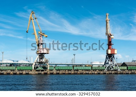Two cranes are loading trains with a coal - stock photo