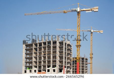Two cranes developing modern residential buildings against blue sky - stock photo