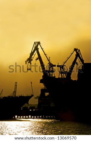 Two cranes sit at rest at an industrial shipyard