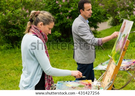 Two creative concentrated painters in a process of  working  on a trestle and easel painting with oils and acrylics during an art class in a forest
