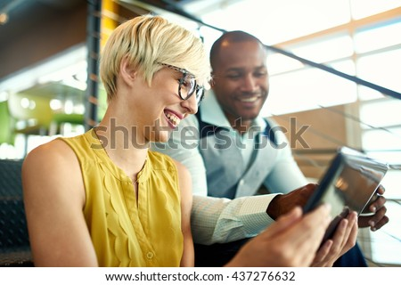 Two creative millenial small business owners working on social media strategy using a digital tablet while sitting in staircase - stock photo