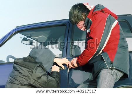 Two crime guys breaking car door - stock photo
