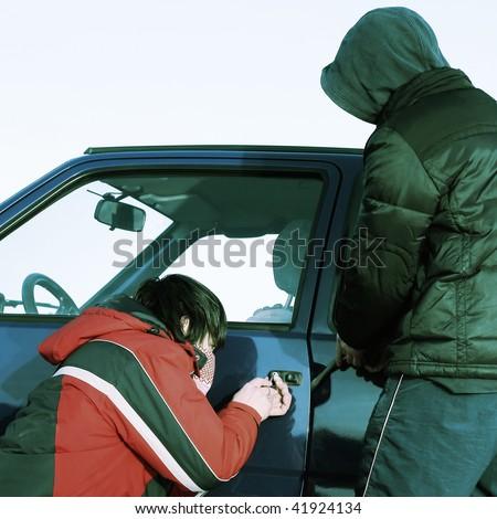 Two crime guys breaking door of a car - stock photo