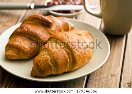 two croissants on a wooden table - stock photo