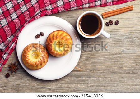 Two cupcake and cup of coffee on wooden table. Top view - stock photo