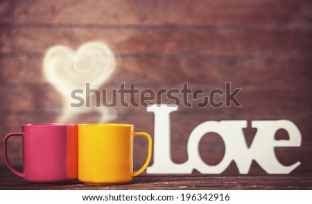 Two cups, abstract heart and word Love on wooden table. - stock photo