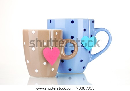 Two cups and tea bags with red and blue heart-shaped label isolated on white - stock photo