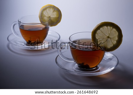 Two cups of black tea with tea leaves and lemon. - stock photo