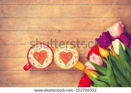 Two cups of Cappuccino with heart shape symbol and tulips on wooden background - stock photo