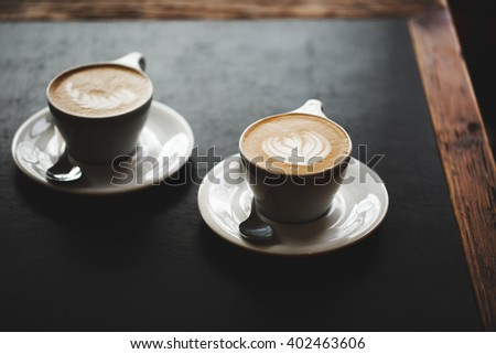 Two cups of cappuccino with latte art on black table. Morning coffee for couple in love. Top view. - stock photo