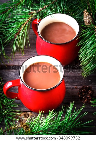 Two cups of cocoa  and pine branches on wooden background. Selective focus.