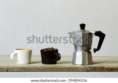 two cups of coffee and beans and percolator on wood