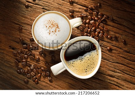 Two cups of coffee and coffee beans on old wooden table - stock photo